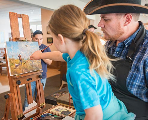 Chad Poppleton gets a little help on his painting for Art In Action.