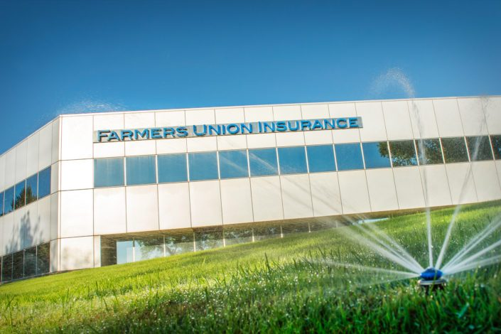 Sprinkler head watering lawn at Farmers Union Insurance